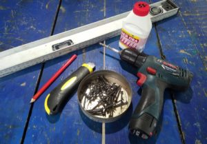 Шуруповерт, шурупы, клей ПВА, строительный нож, карандаш и уровень лежат на столе